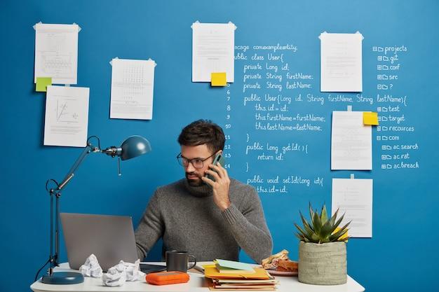 랩톱 컴퓨터 화면에 집중하고 정보 분석에 집중 한 진지한 남성 디자이너, 원거리 작업 중 보고서에 대해 생각
