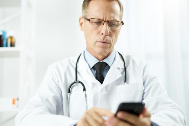 직장에서 휴대 전화를 사용하는 심각한 남성 의사