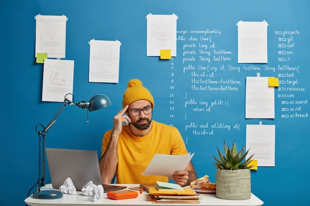 진지한 남성 직원 또는 프리랜서는 종이 문서를 고려하고, 노란색 모자와 티셔츠를 입고, 온라인에서 랩톱 컴퓨터를 공부하고, 집에서 일하고, 자료를 살펴보고, 코 워킹 공간에서 포즈를 취합니다.