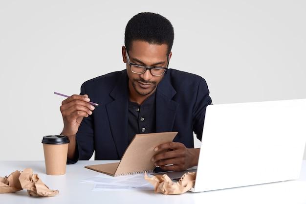 暗い健康な肌を持つ深刻な男性従業員、ペンを持ち、日記にメモを書き、リストを作成し、来週の仕事を計画し、ポータブルラップトップコンピューターでプレゼンテーションを行い、コーヒーを飲み、分離
