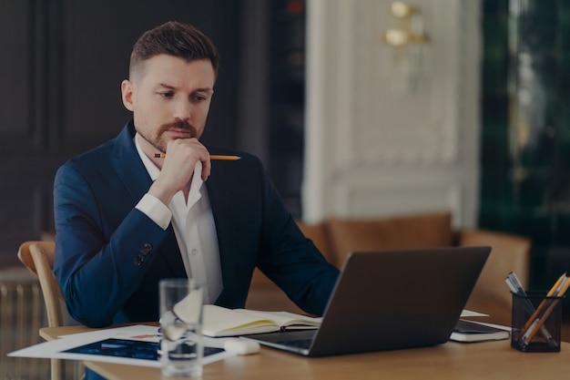 真面目な男性起業家はあごを持ってラップトップコンピューターの日記にメモを書き、オンラインでお金を稼ぎ、正式に情報を書きます。作業プロセスに関与する自信のあるマネージングディレクター