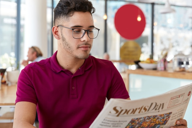 Serious male entrepreneur starts day with morning newspaper, analyzes news in press, wears optical glasses for good vision, wears casual t shirt, concentrates on reading article in cafeteria.