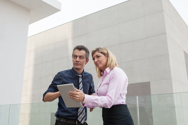 Serious male and female business people using tablet computer outdoors.