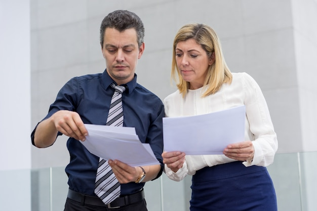 Colleghi maschii e femminili seri che discutono i documenti all'aperto.