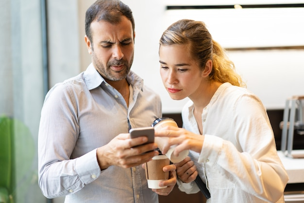 Serious male and female colleagues reading message on cellphone