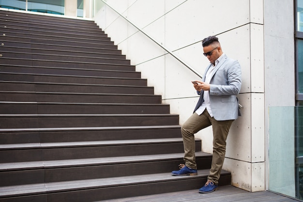 Serious male freelancer checking message on phone