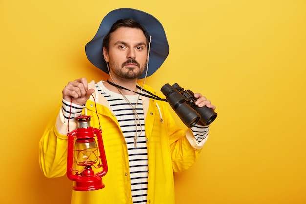 Serious male hiker carries gas lamp, uses binoculars during hiking trip, dressed in raincoat, looks confidently at camera isolated over yellow wall