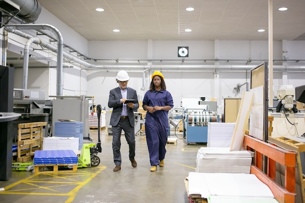 Серьезный инспектор-мужчина и работница фабрики в касках гуляют по цеху и разговаривают, мужчина использует планшет