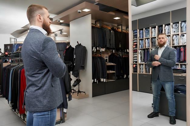 Серьезный мужчина смотрит в зеркало и выбирает нарядный костюм