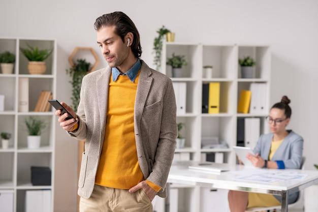 Серьезный мужчина-менеджер в беспроводных наушниках стоит в офисе и использует смартфон, общаясь с клиентом через мессенджер