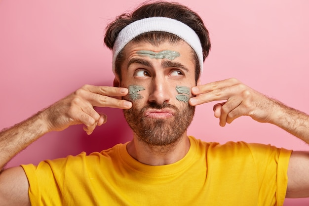 Serious male model applies cosmetic mud mask on face, wears white headband, yellow t shirt, cares about skin, looks sadly aside, tired of daily beauty routine