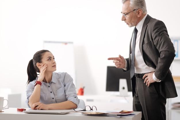 新しい同僚を批判しながら女の子を指してベルトに左手を保つ真面目な男性