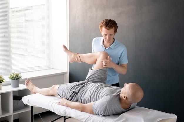 Серьезный физиотерапевт-мужчина смотрит на своего пациента с согнутой в колене ногой, помогая ему с одним из физических упражнений в реабилитационном центре