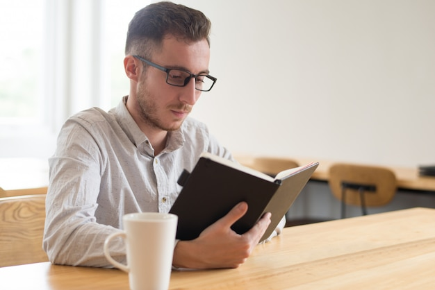 Serious male student reading textbook at table in cafe