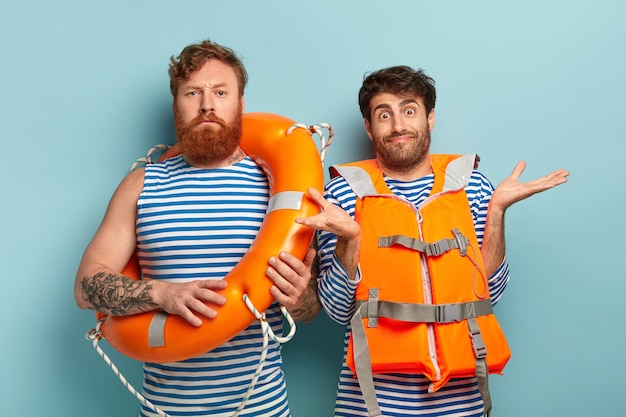 ライフラインを持つ真面目な男性水泳インストラクター、疑わしい研修生はオレンジ色のベストを着て、手を広げます