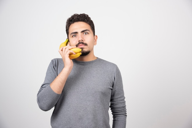 Maschio serio parlando con banana su grigio.