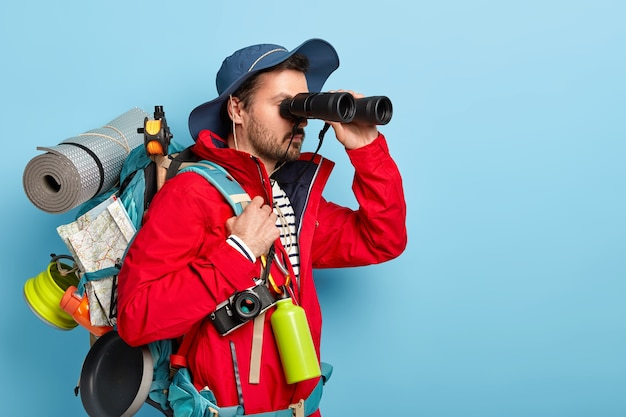 Serious male tourist uses binoculars to observe surroundings, carries rucksack with rolled up rag, map and pan for cooking on bonfire