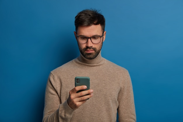 真面目な男性は現代のスマートフォンを使用し、青い背景で隔離のディスプレイを注意深く見つめています。