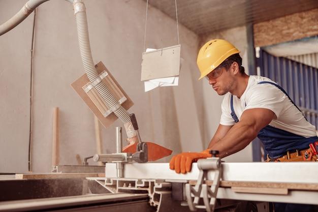 작업장에서 목공 장비를 사용하는 진지한 남성 노동자 프리미엄 사진