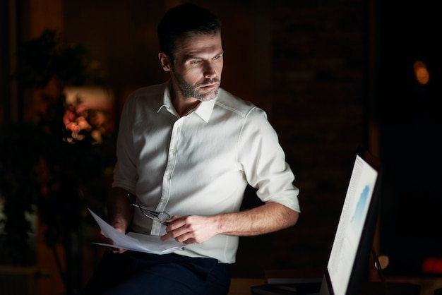 Серьезный мужчина анализирует документ в своем офисе