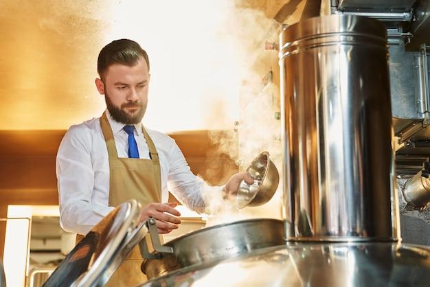 Серьезный человек варит пиво. профессиональный пивовар в белой рубашке и фартуке, работающий на заводе по производству пива и контролирующий процесс производства эля. концепция ликероводочного завода и напитков.