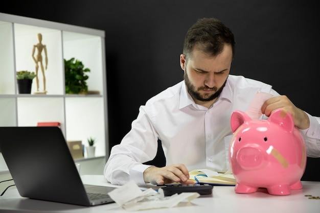 Serious man calculate bills at home office with broken piggy bank with plasters