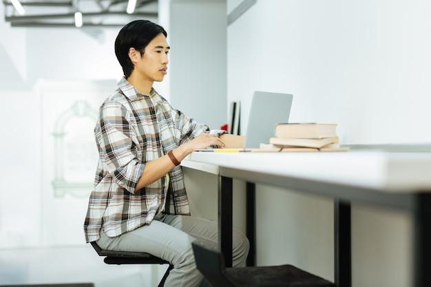 Серьезный человек. спокойный сосредоточенный азиатский человек сидит за столом в современном коворкинге и работает за своим ноутбуком.