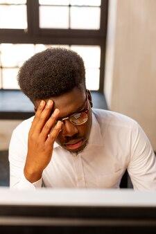 사무실에 앉아있는 동안 그의 일에 집중하는 심각한 남자