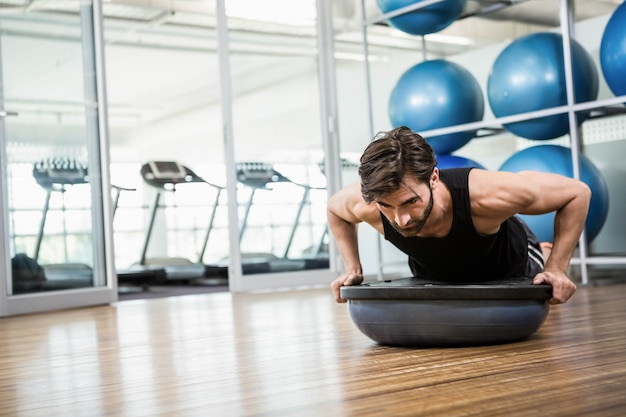 Serious man doing exercise with bosu ball in the studio