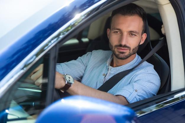 運転中の真面目な男。彼の車を運転している間気分が良い深刻なハンサムなひげを生やした男