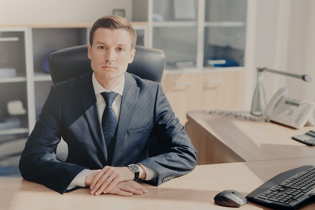 Serious man in formal suit sits at work place in cozy cabinet at office