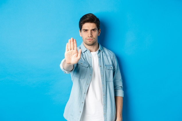 심각한 남자 인상을 찌푸리며 아니오라고 말하고 상점 정지 표지판으로 손을 내밀고, 행동을 금지하고, 파란색 배경에 서서