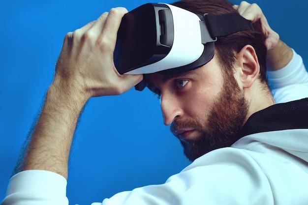 Серьезный геймер, готовый надеть очки vr на изолированной синей стене