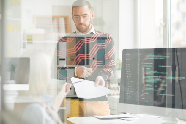 プログラマーの女性にコード付きの論文を与える深刻な男