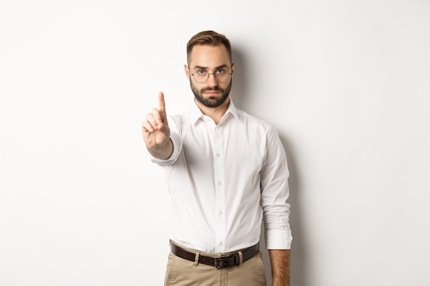 Serious man in glasses showing stop sign, shaking finger to prohibit and forbid, standing  white