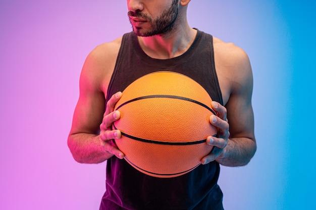 真面目な男がバスケットボールのボールを手に持っています。若いひげを生やした男の着用タンクトップのトリミングされた画像。青とピンクの背景に分離。スタジオ撮影