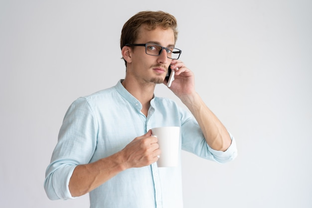 Serious man holding mug and talking on smartphone