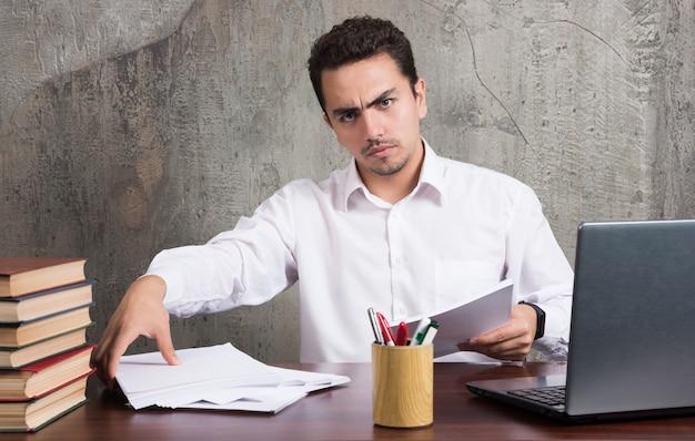 Серьезный мужчина держит листы бумаги и сидит за столом. фото высокого качества