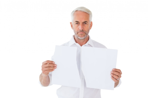 Serious man holding torn sheet of paper