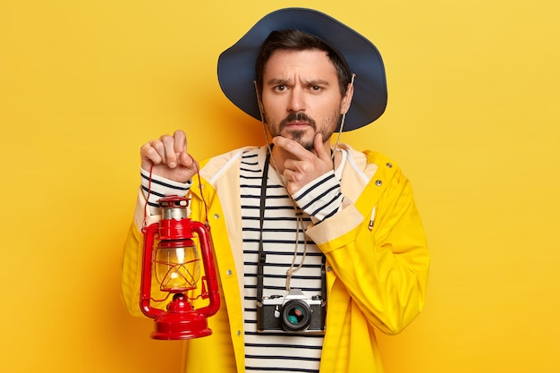 Serious man holds chin, thinks about something, carries kerosene lamp, has retro camera hanging around neck, enjoys travel in mountains or forest, dressed in raincoat isolated on yellow