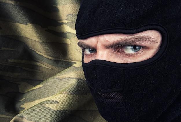 Серьезный мужчина в маске-балаклаве на фоне военного камуфляжа