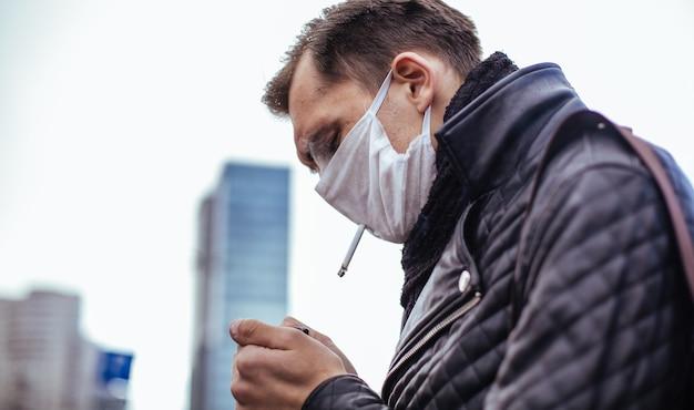 보호 마스크에 심각한 남자가 거리에 서 담배