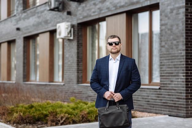 街の通りのシーンでバッグとメガネのスーツを着た真面目な男