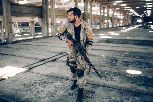メガネの深刻な男は格納庫に立って、ペイントボール銃を手に持っています。