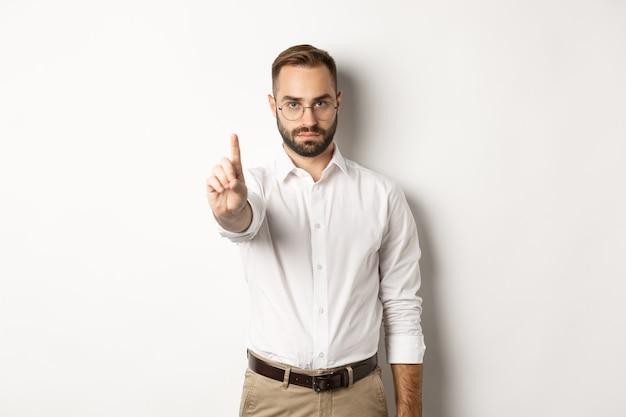 Серьезный мужчина в очках показывает знак остановки, трясет пальцем, чтобы запретить и запрещать, стоит белым