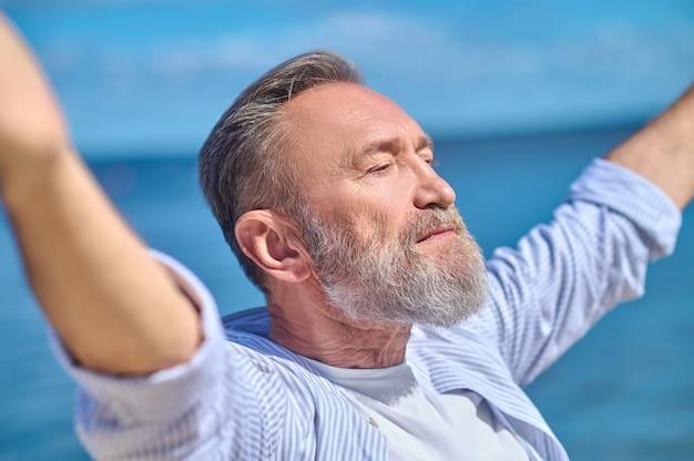 Серьезный мужчина в гармоничном настроении на открытом воздухе