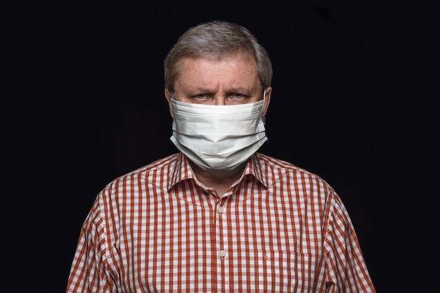 黒の背景に保護マスクの深刻な男。肺炎の予防、検疫を続け、家にいる。中国のコロナウイルス治療。ヘルスケア、医学、隔離の概念。