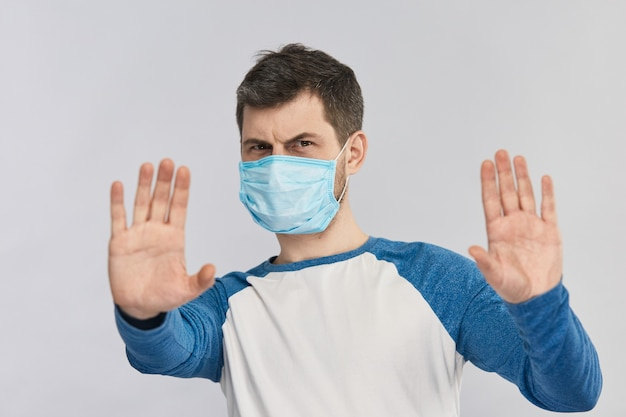 두 손으로 중지를 보여주는 호흡 마스크에 심각한 남자 공간을 복사합니다. 사회적 거리두기, 코로나 19 예방