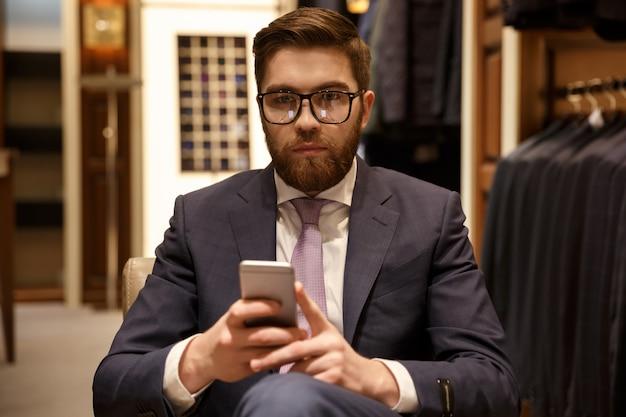 スーツと眼鏡の携帯電話を保持している深刻な男