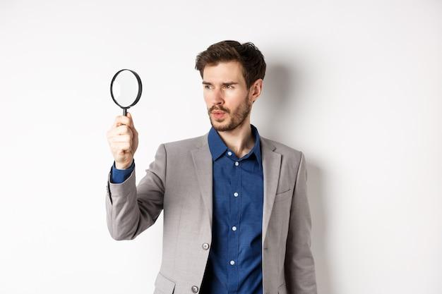 Серьезный мужчина в костюме ищет улики через увеличительное стекло, расследуя, стоя на белом фоне.